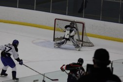 Hawks goaltender, Aaron Karkos, comes up with the save